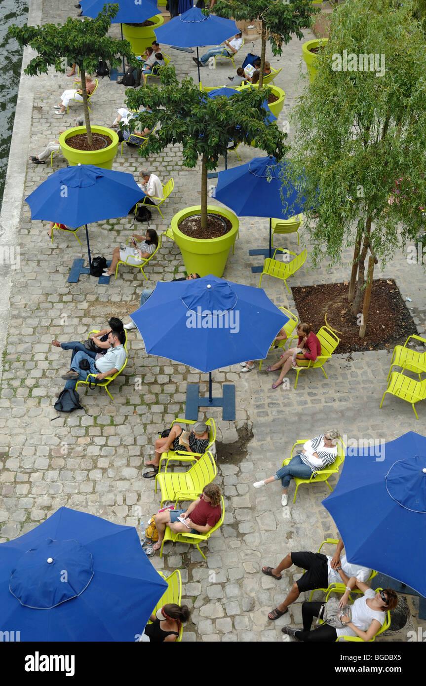 People Relaxing, Blue Parasols & Deckchairs Along Quai of the River Seine during 'Paris-Plage' Events, Paris, France Stock Photo