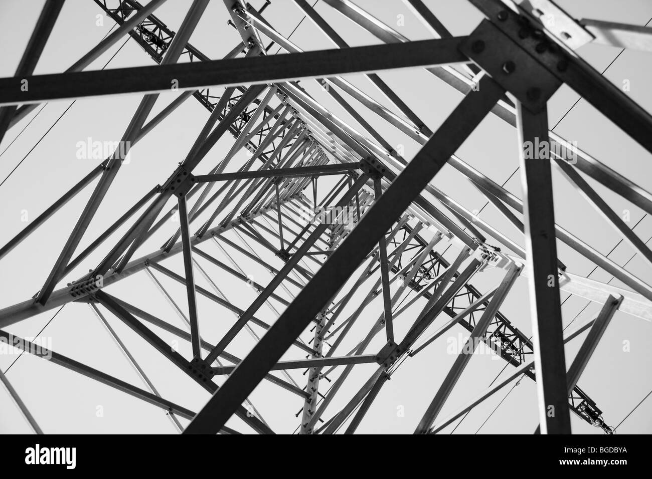 View from below looking up in an electricity pylon, black and white - Stock Image