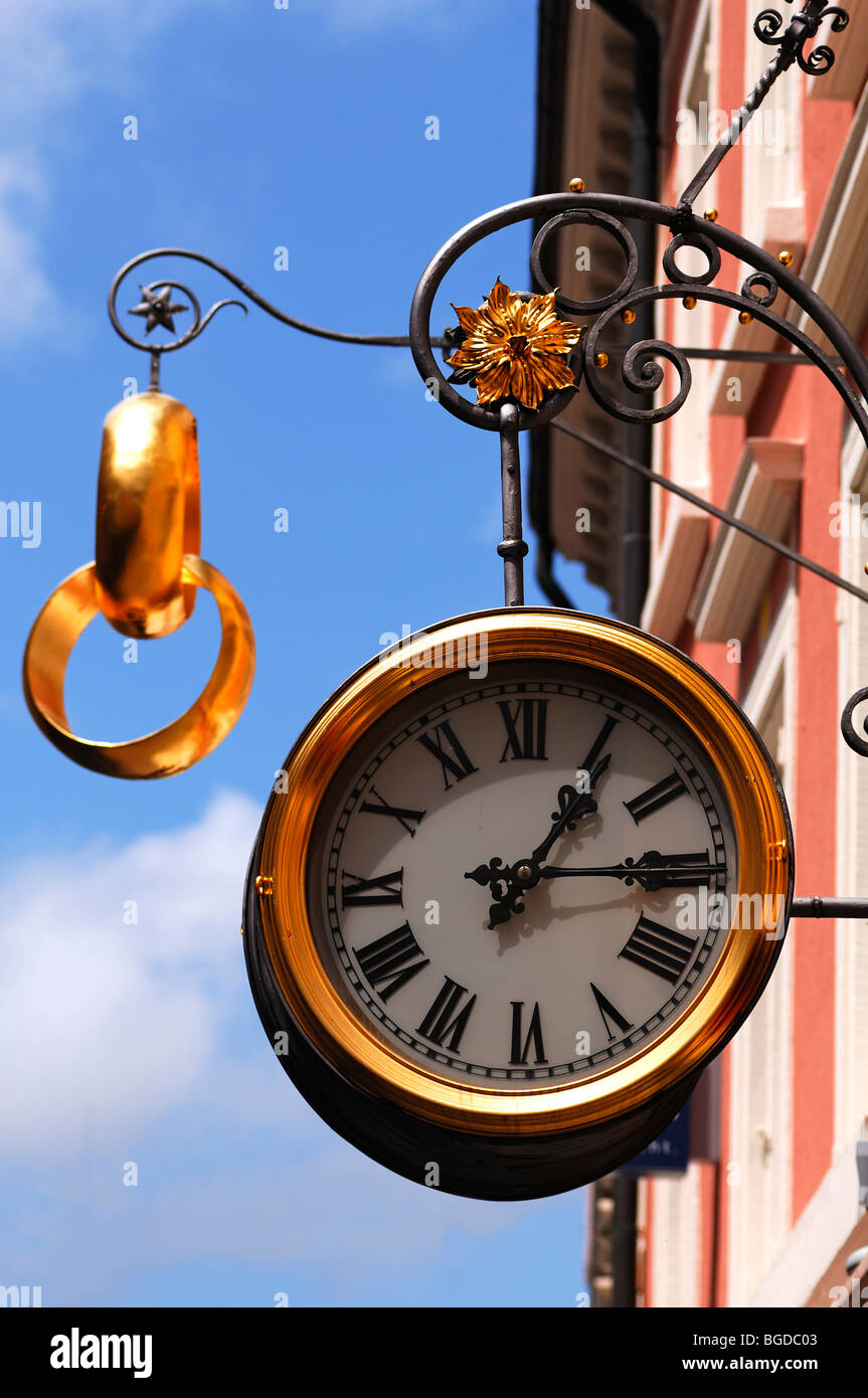 Large clock and two gold wedding rings as a sign outside a jewellery store, Freiburg im Breisgau, Baden-Wuerttemberg, - Stock Image