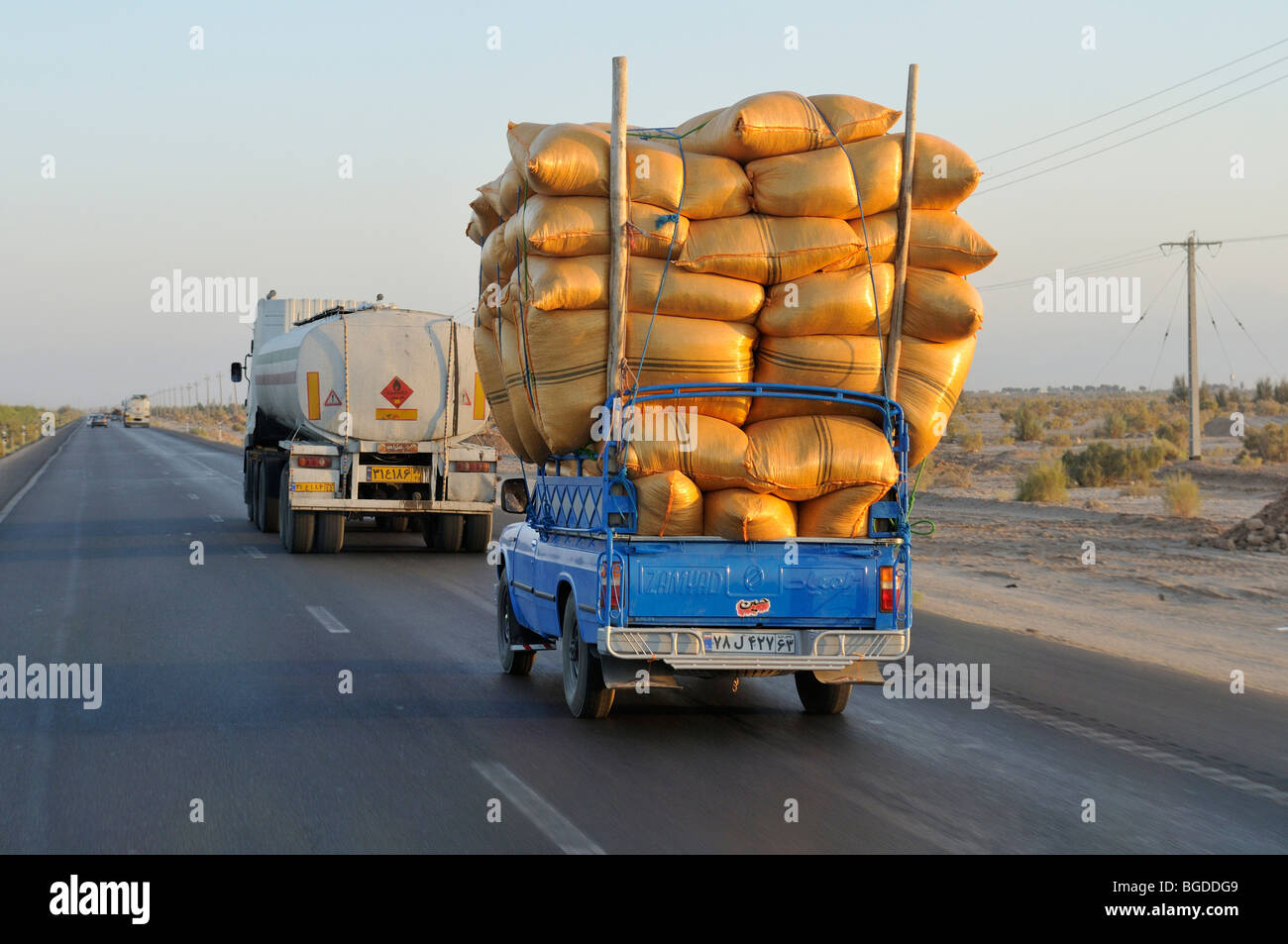 Iranian pickup truck overloaded with sacks on a highway, Iran, Persia, Asia - Stock Image