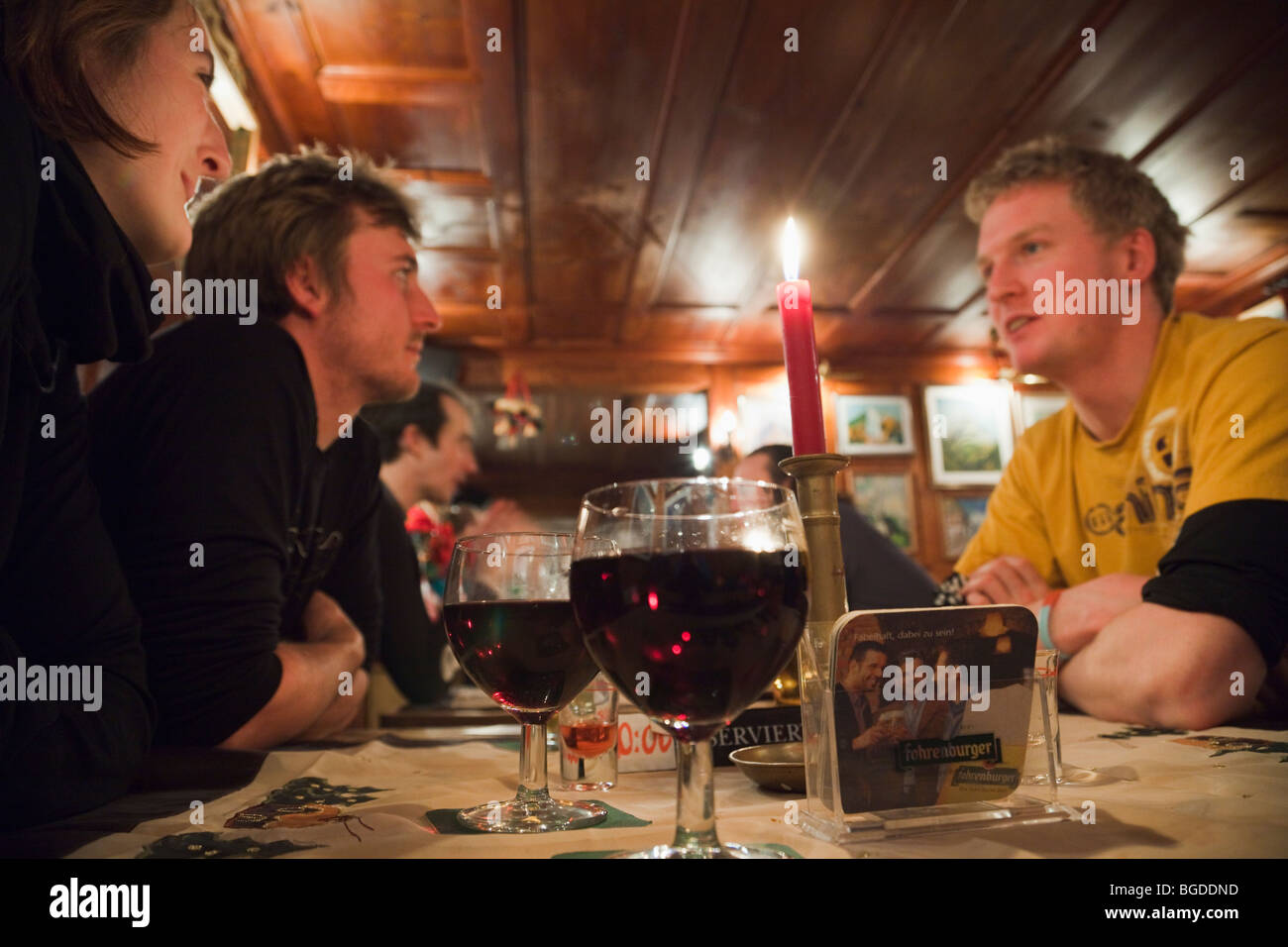 Young people Millennials sat drinking red wine around a table in 'The Underground' apres ski bar in St Anton - Stock Image