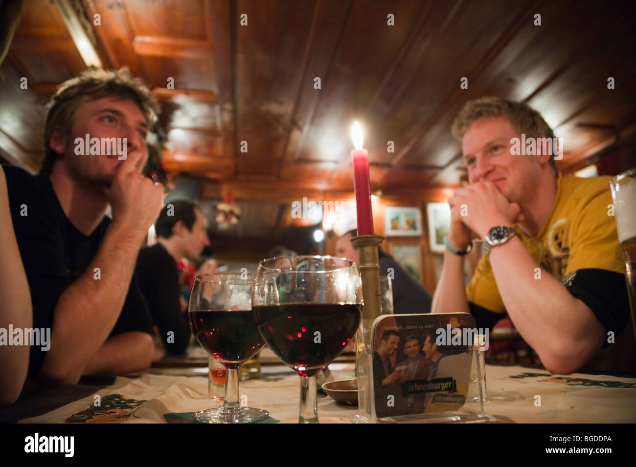 Young people friends sat drinking red wine around a table in 'The Underground' apres ski bar in St Anton, - Stock Image