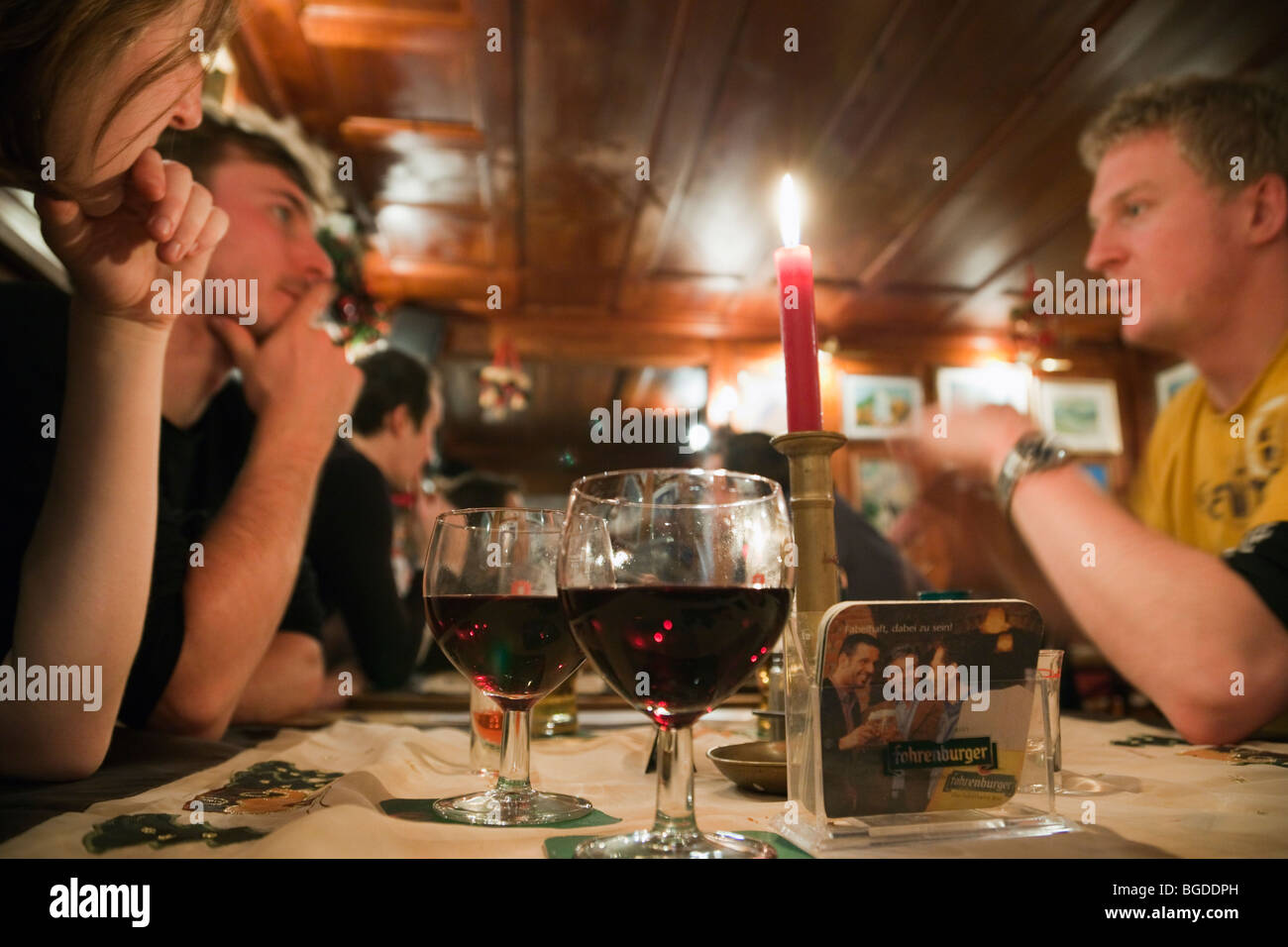 Everyday hygge scene of young people sat drinking wine around a table in a bar. Modern lifestyle. Austria, Europe. - Stock Image