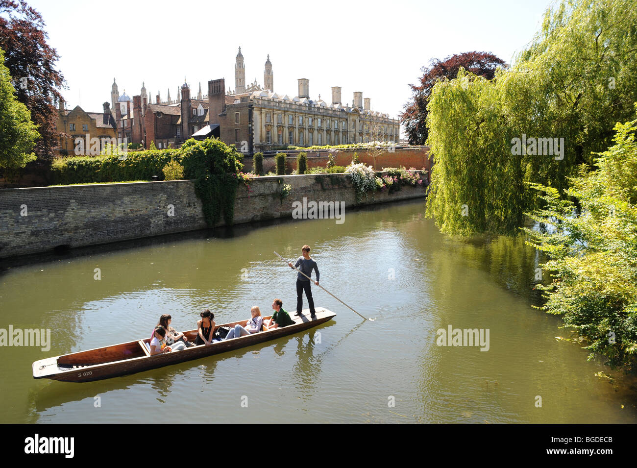 Tourists enjoy a warm summer punt ride on the River Cam behind Trinity College, Cambridge University, Cambridge, - Stock Image