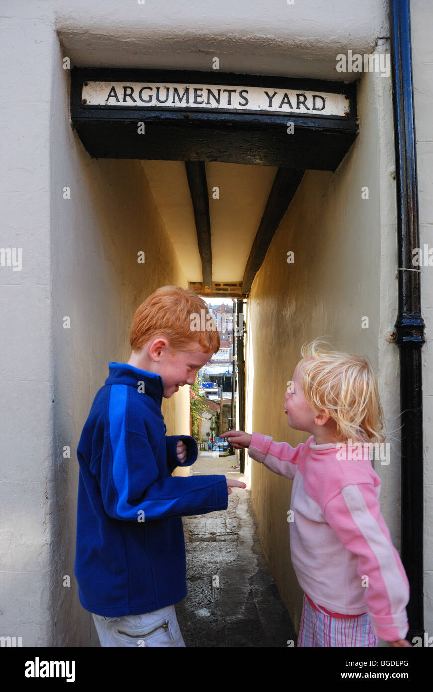 Children having an argument in Arguments Yard, a street in Whitby, England - Stock Image