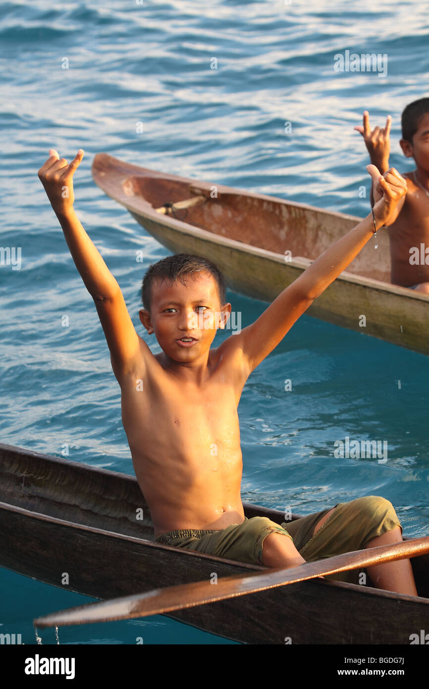 Happy boys in their dugout canoes. Sipora Island, Mentawai Islands, Sumatra, Indonesia, Southeast Asia - Stock Image