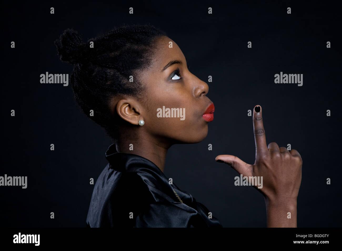 Teenage girl pretending to blow the smoke off a gun. Stock Photo