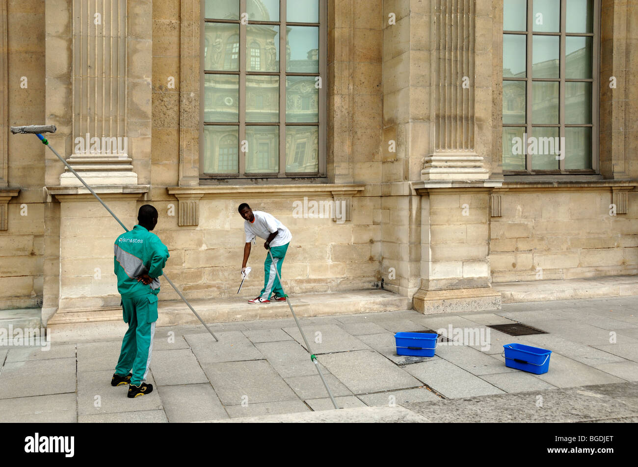 African Immigrant Workers Cleaning Windows of the Louvre Museum, Paris, France - Stock Image