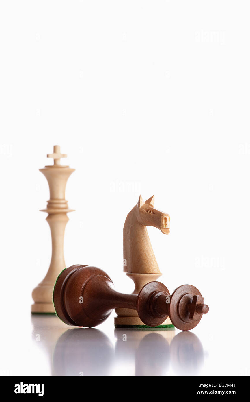 chess - white knight standing over defeated black king - Stock Image