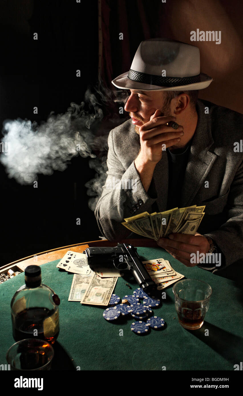 portrait of young gangster smoking and play poker - Stock Image