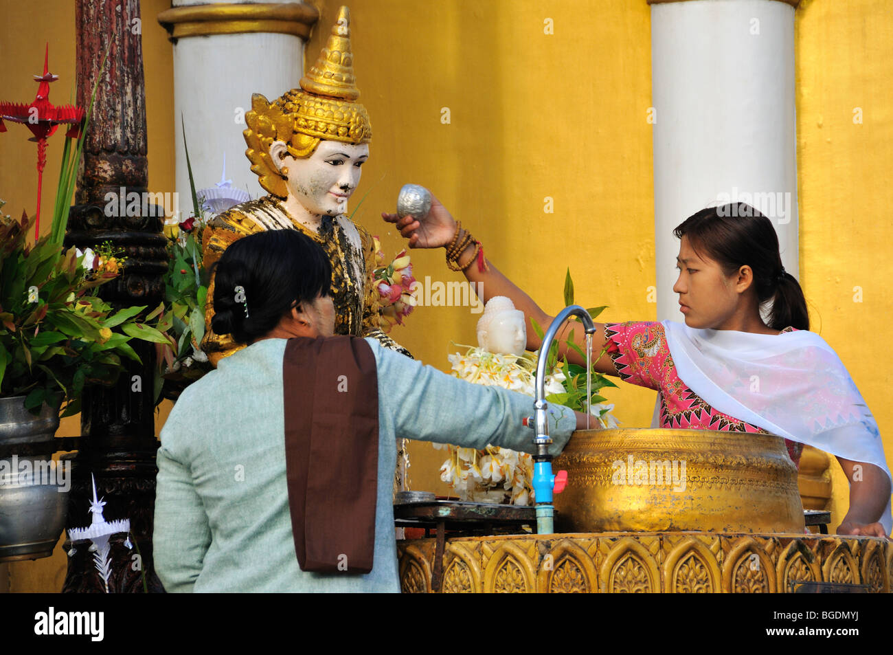 Women pouring water on Statue, Shwedagon Pagoda, Yangon, Burma, Myanmar - Stock Image