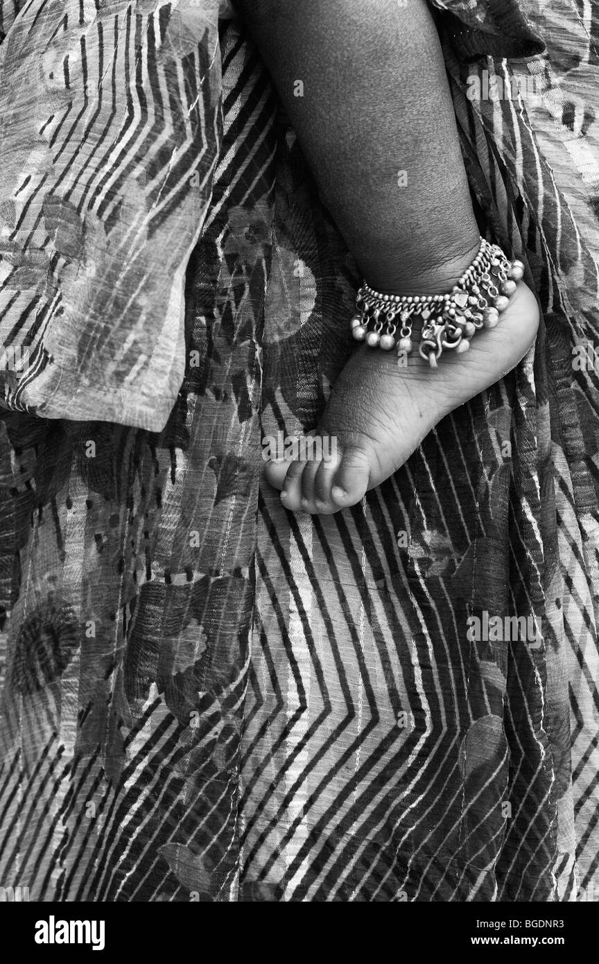 Indian babies bare foot wearing an ankle bracelet against mothers striped patterned sari. Andhra Pradesh, India. - Stock Image