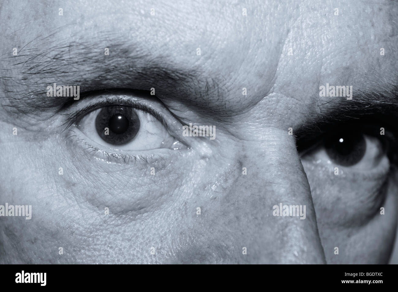 Sinister looking close up of an old mans eyes in monochrome - Stock Image