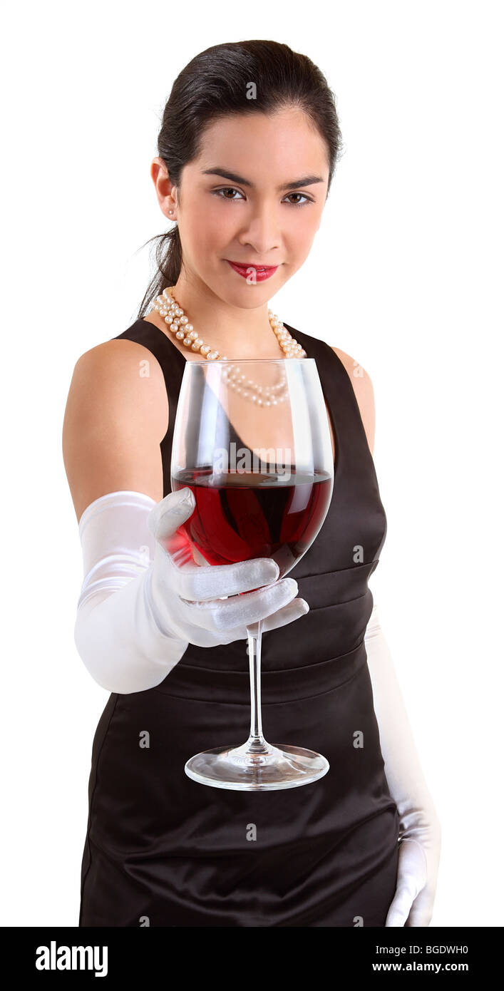 A beautiful woman in a classy dress is serving a glass of red wine. - Stock Image