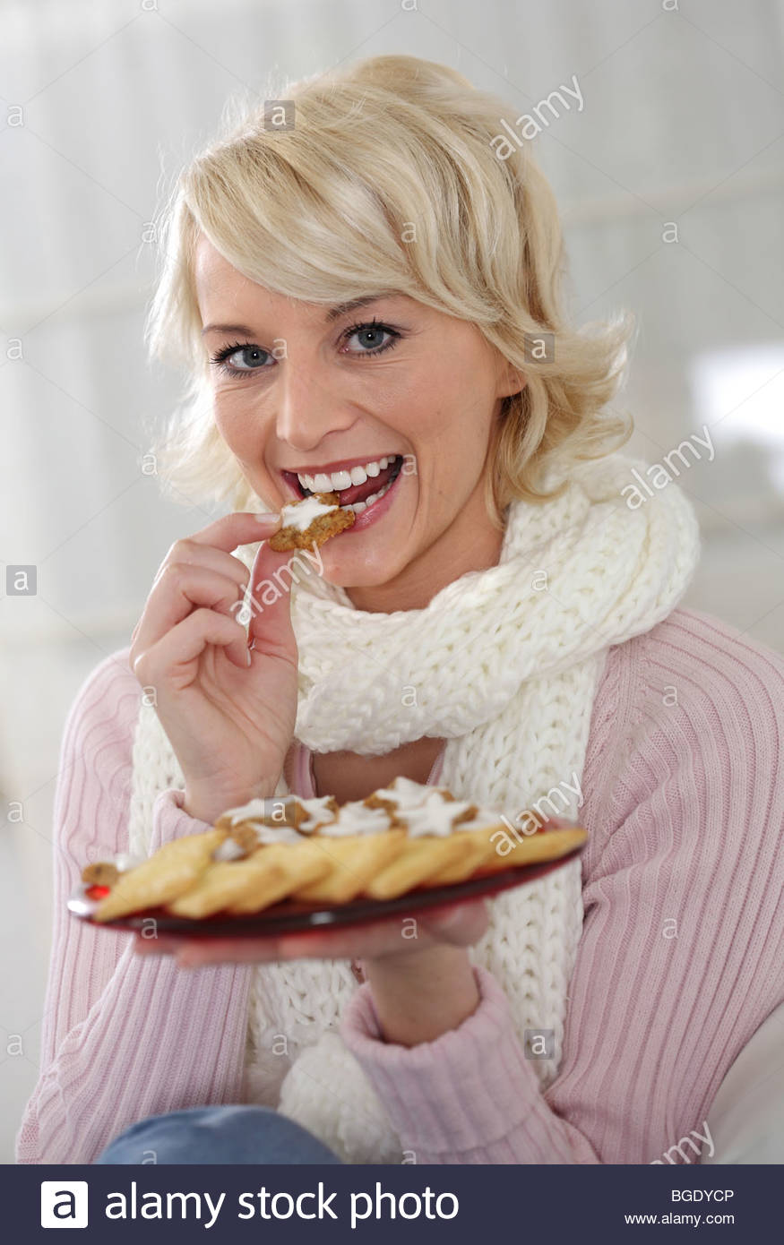 young blond woman eating christmas cookies - Stock Image