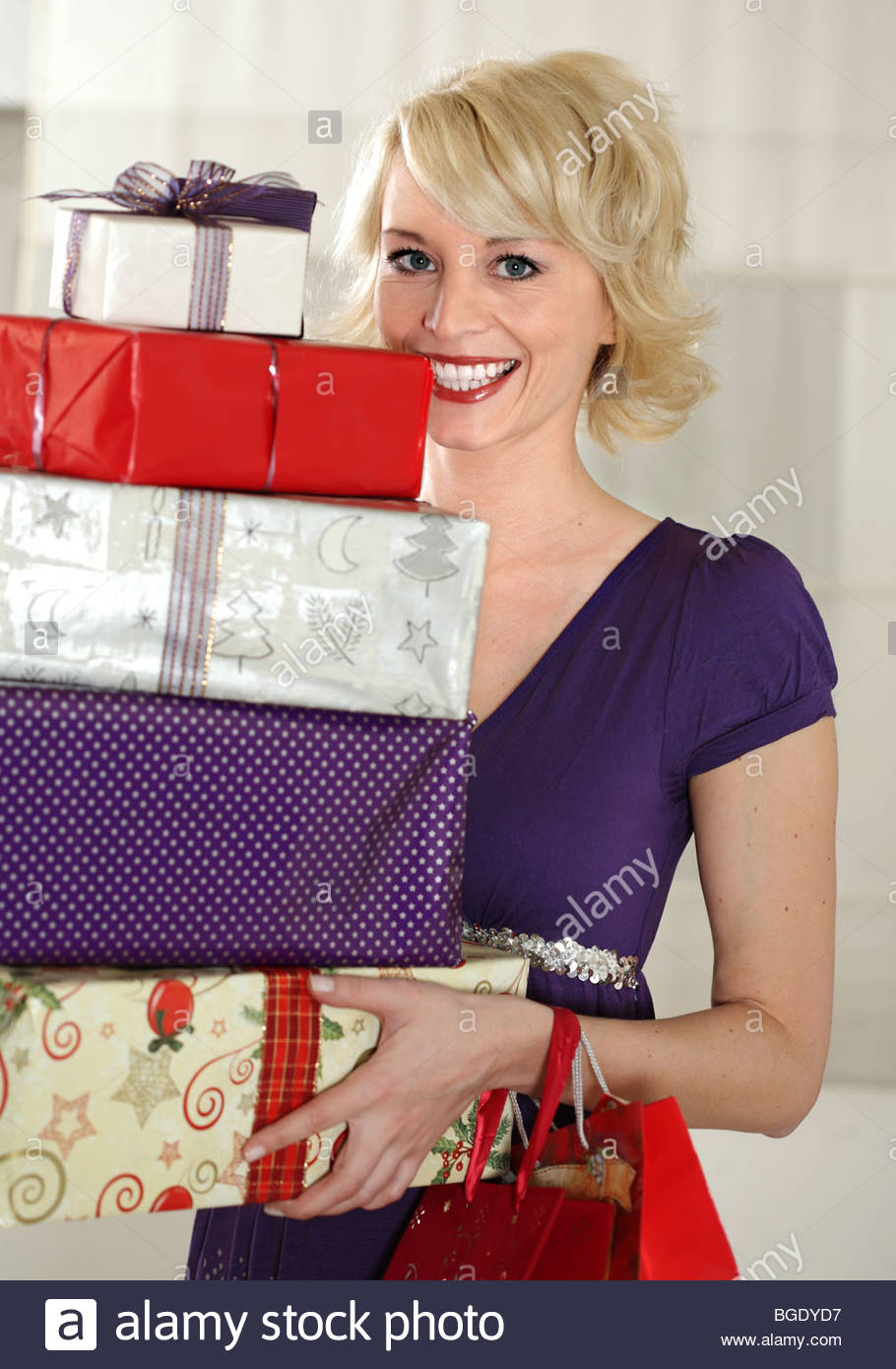 young blond woman holding christmas gifts in her hand - Stock Image