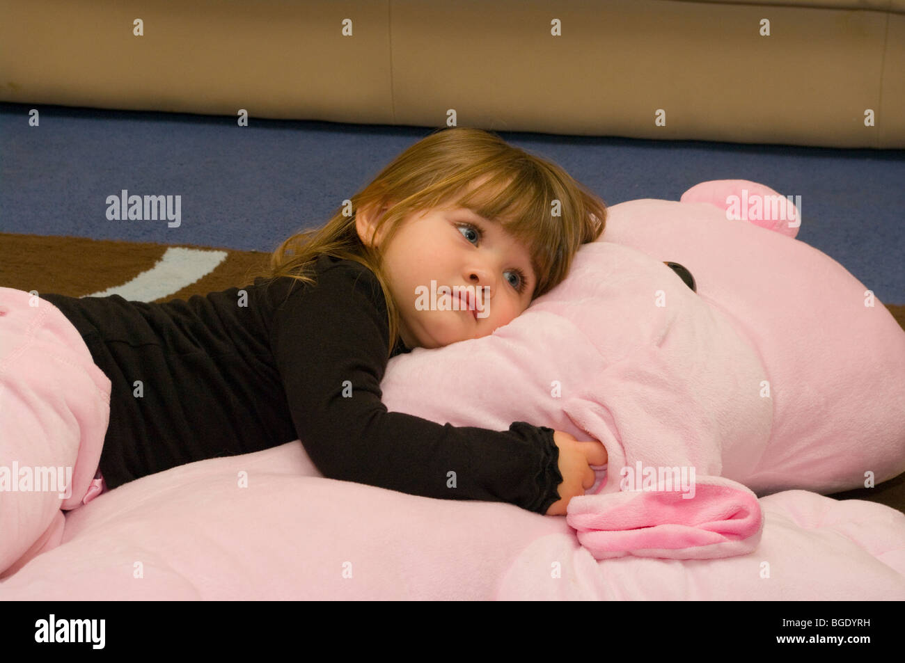 Baby Girl Laying On A Big Pink Beanbag - Stock Image