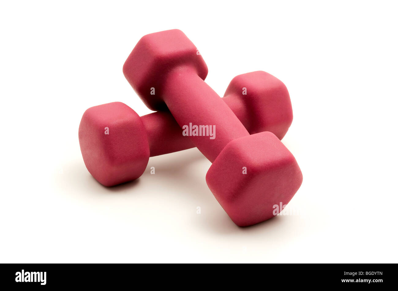 Pink fixed-weight dumbbells on a white background - Stock Image