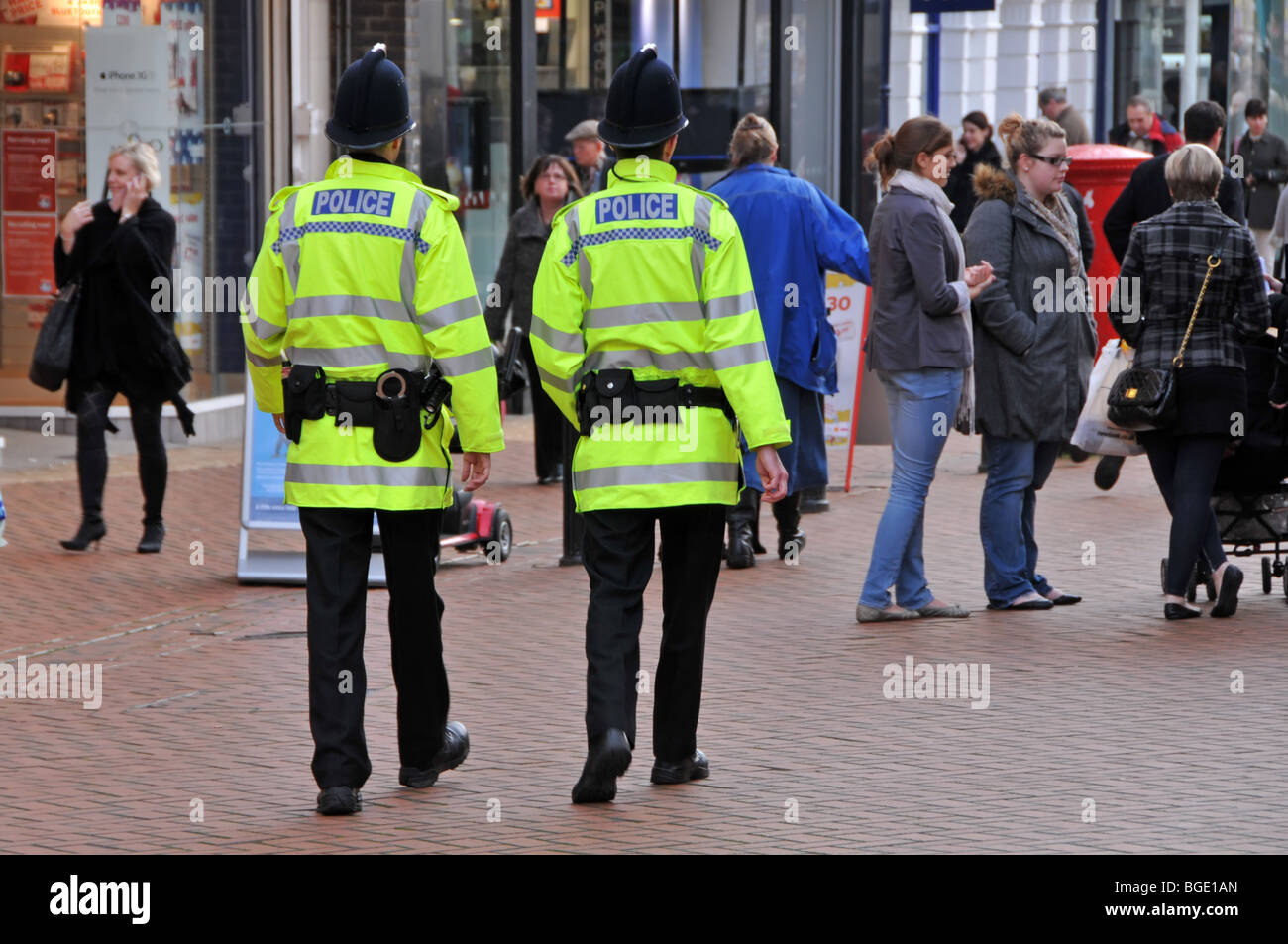 Two policemen on patrol in busy shopping high street - Stock Image