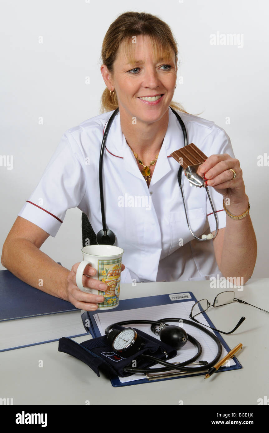 Portrait of a female nurse seated at her desk drinking coffee and eating a chocolate KitKat bar - Stock Image