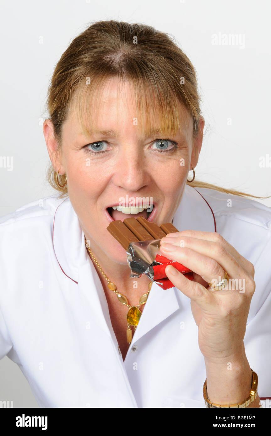 Woman eating a chocolate KitKat bar - Stock Image