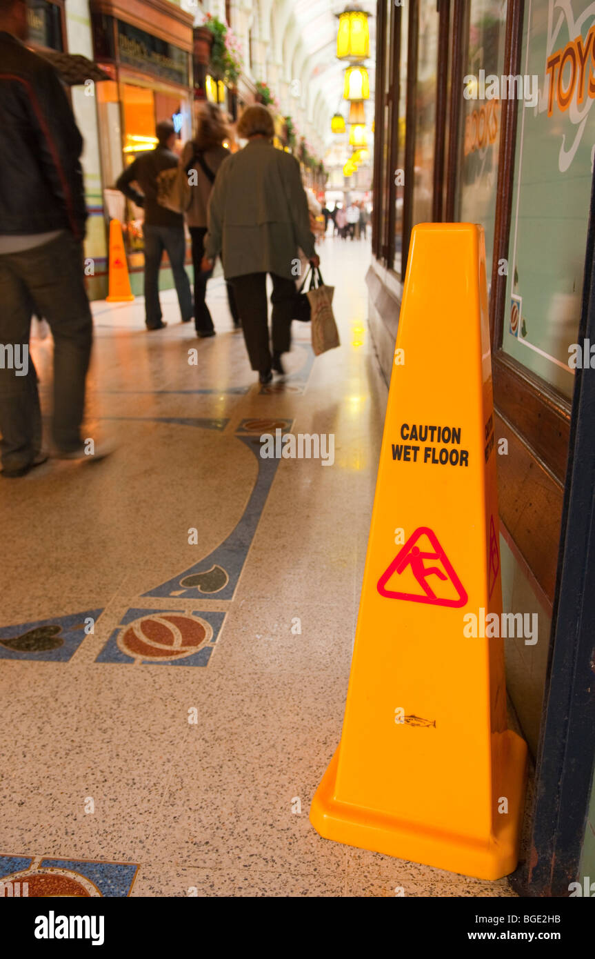 Shoppers in the royal arcade walk past a warning sign of a wet floor in the city centre of Norwich,Norfolk,Uk - Stock Image