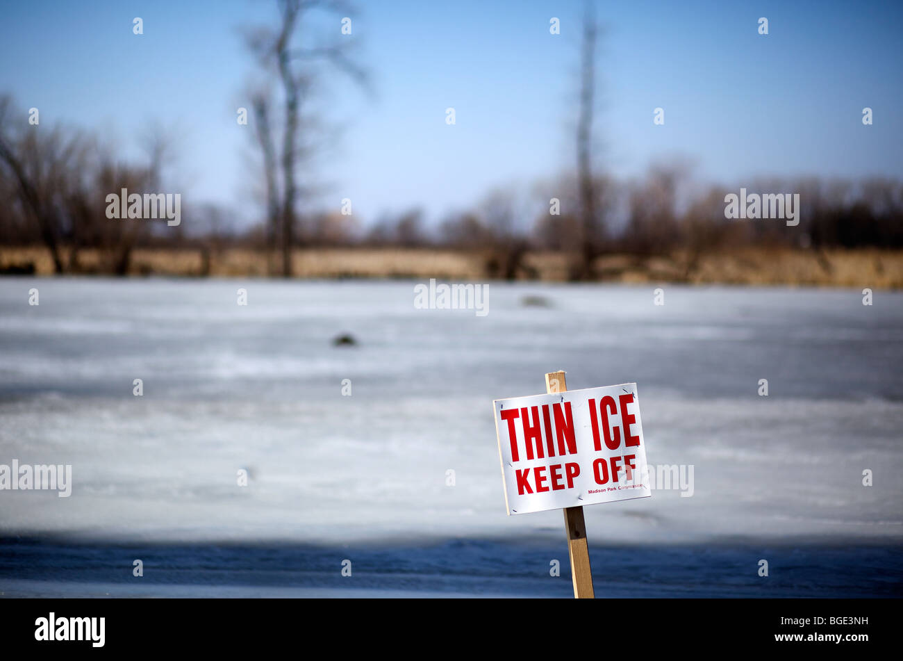 Thin ice sign on pond in Madison, Wisconsin. - Stock Image