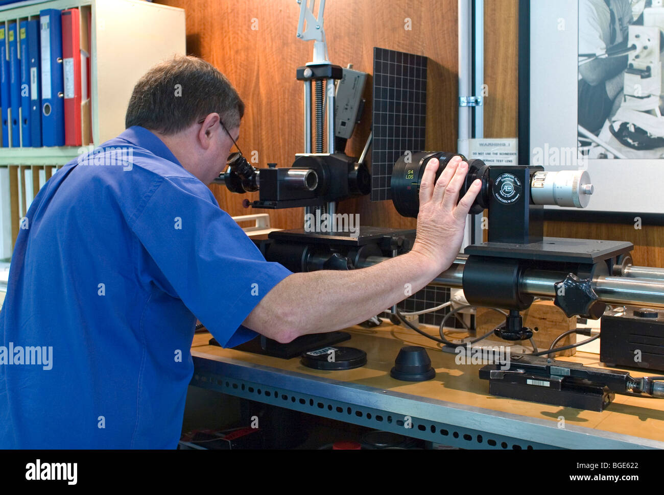 Lens Technician checking a lens on an Autocollimator - Stock Image