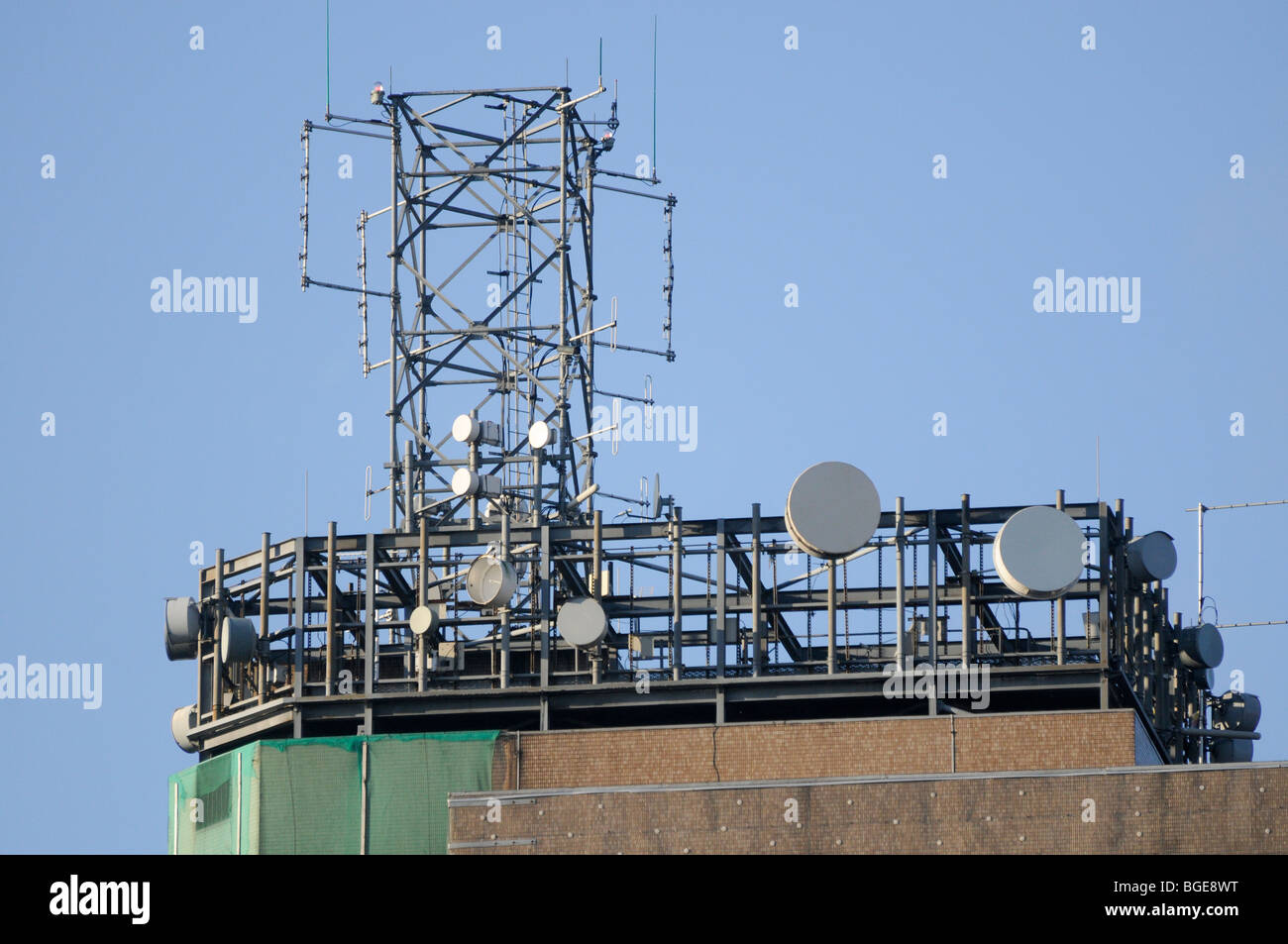 Set of telecommunications/telecoms antenna including RF, PMR, cellular, SDH and PDH microwave dishes on a tall building. - Stock Image