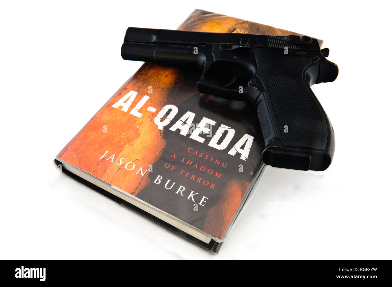 Handgun sitting on top of a book 'Al-Qaeda' by Jason Burke - Stock Image