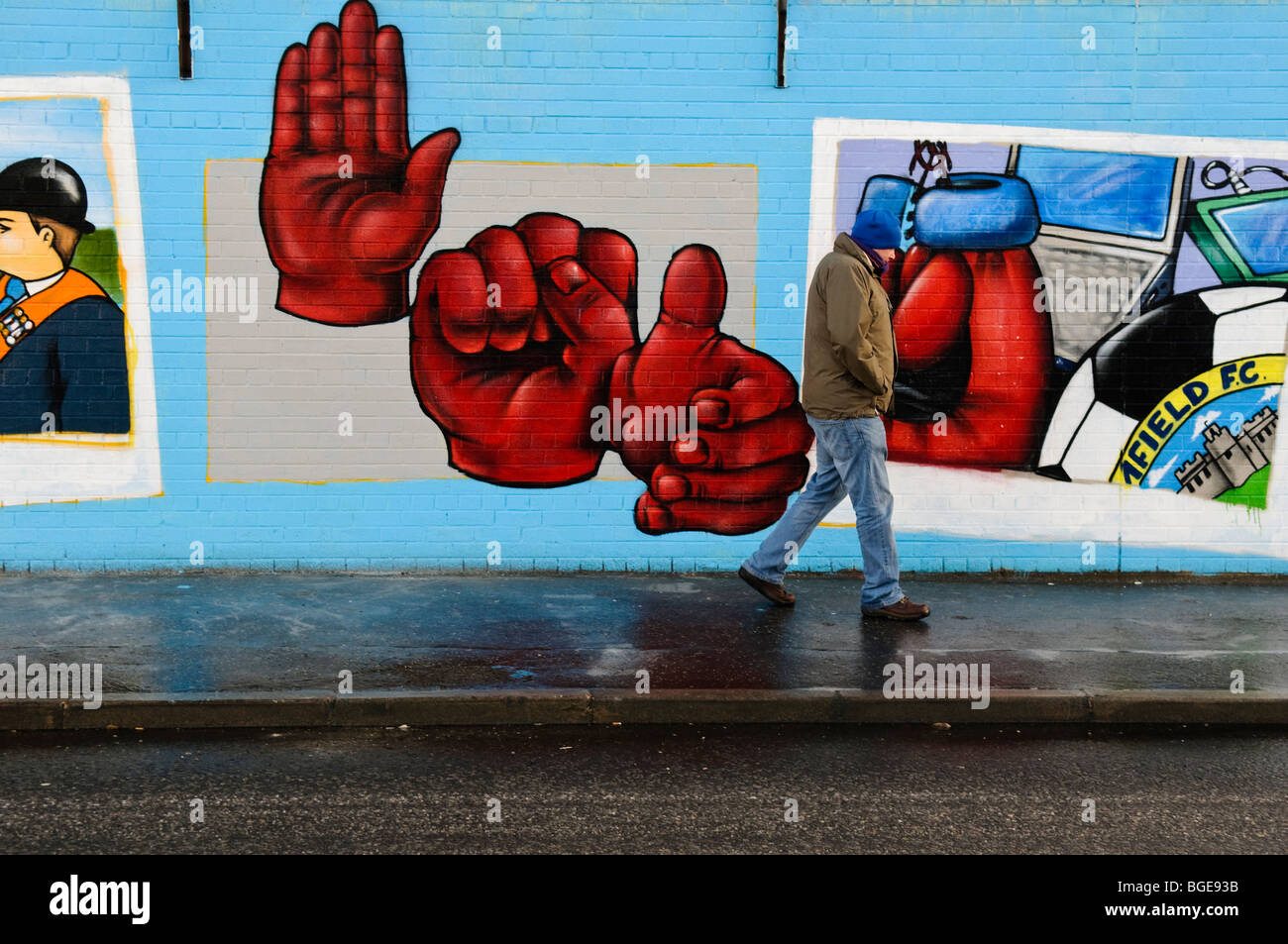 Man walks past new murals, painted at the start of 2010 on the loyalist end of Northumberland Street, Shankill Road, Stock Photo
