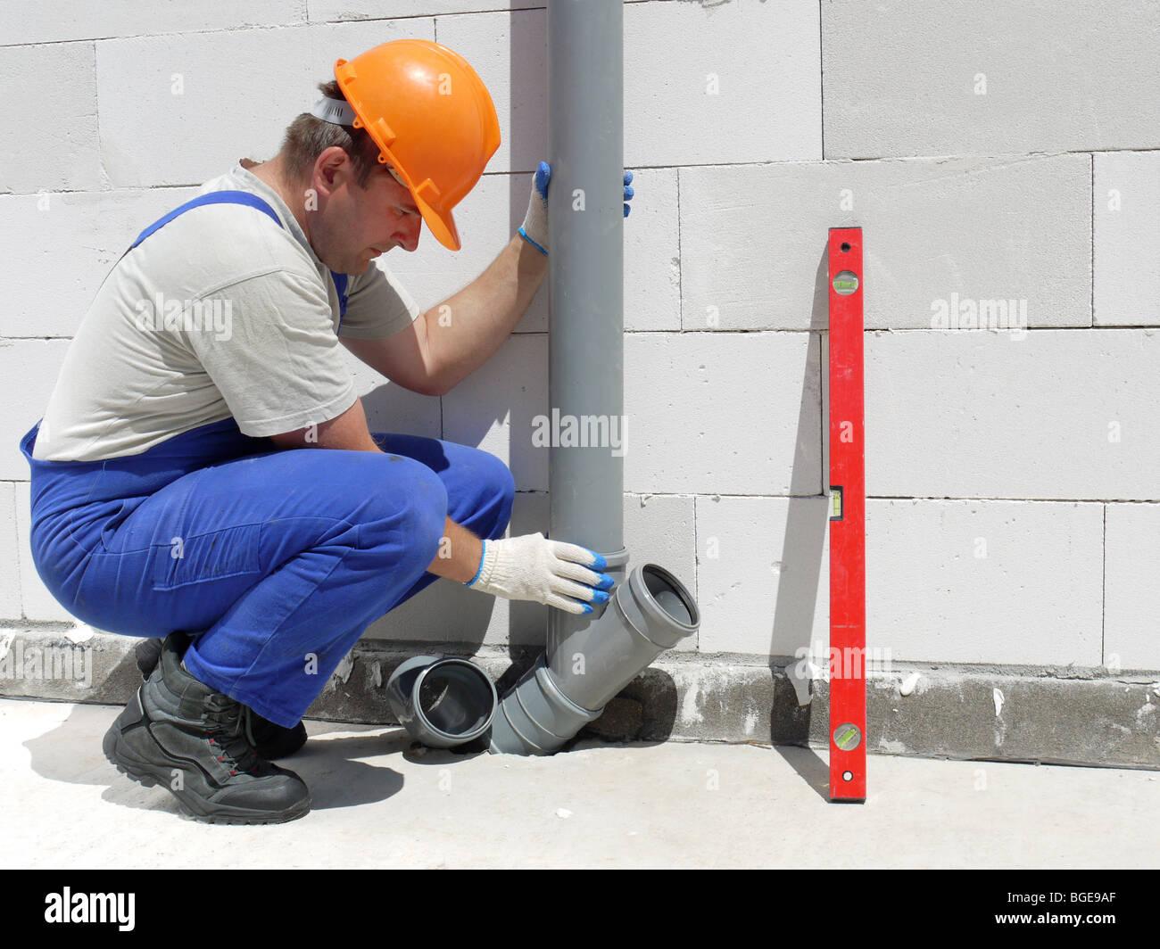 Plumber assembling pvc sewage pipes inside unfinished house - Stock Image