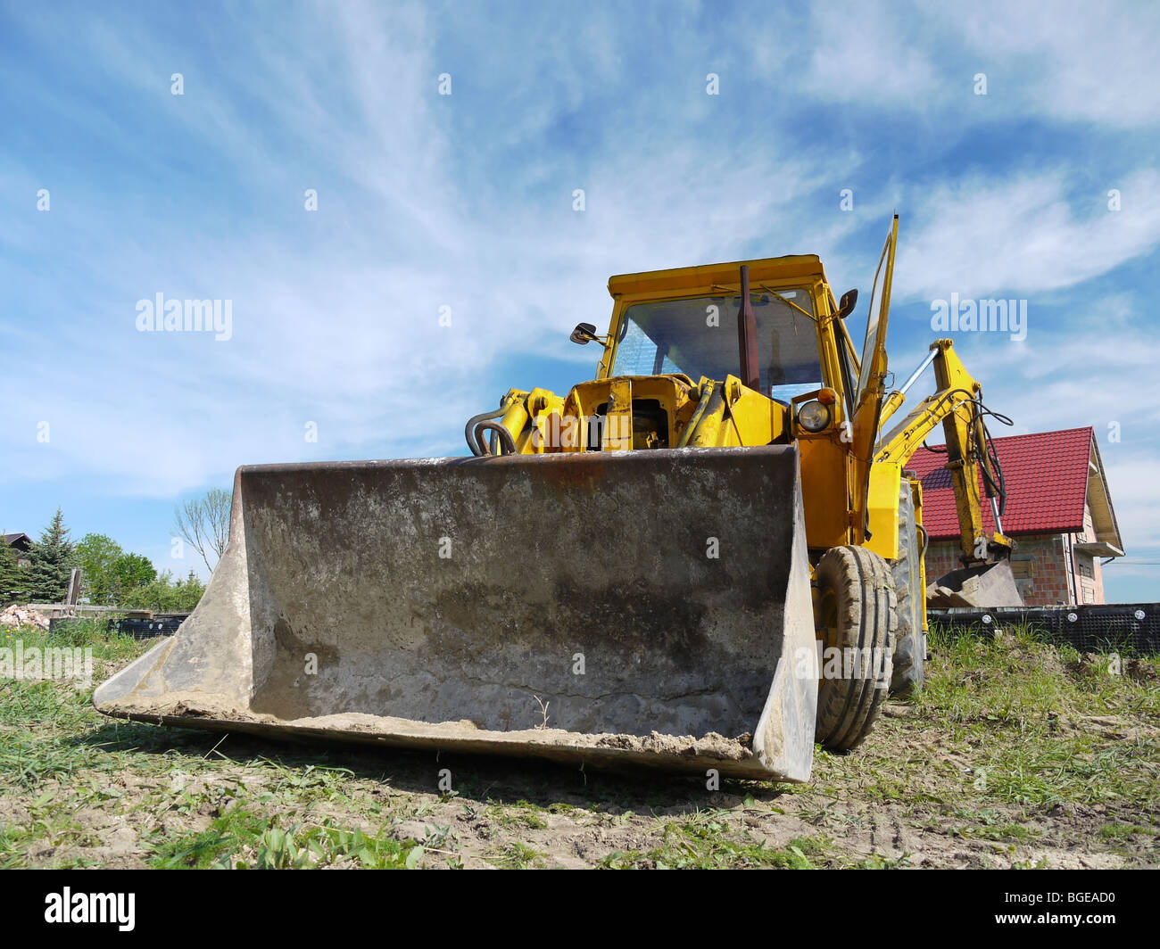 Yellow backhoe loader parked at construction site - Stock Image