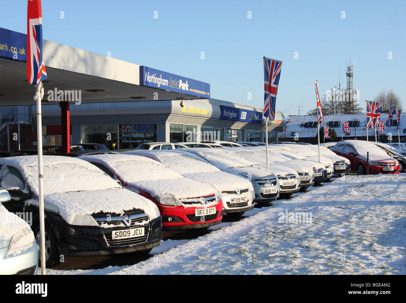 Snow covered cars for sale at a car dealership in a U.K. city. - Stock Image