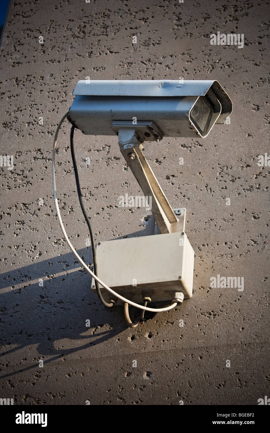 A security camera, photographed against the concrete wall it's mounted on. Stock Photo