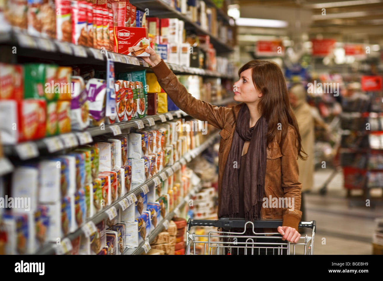A woman in a grocery store grabbing a packet of crackers off the shelf. - Stock Image