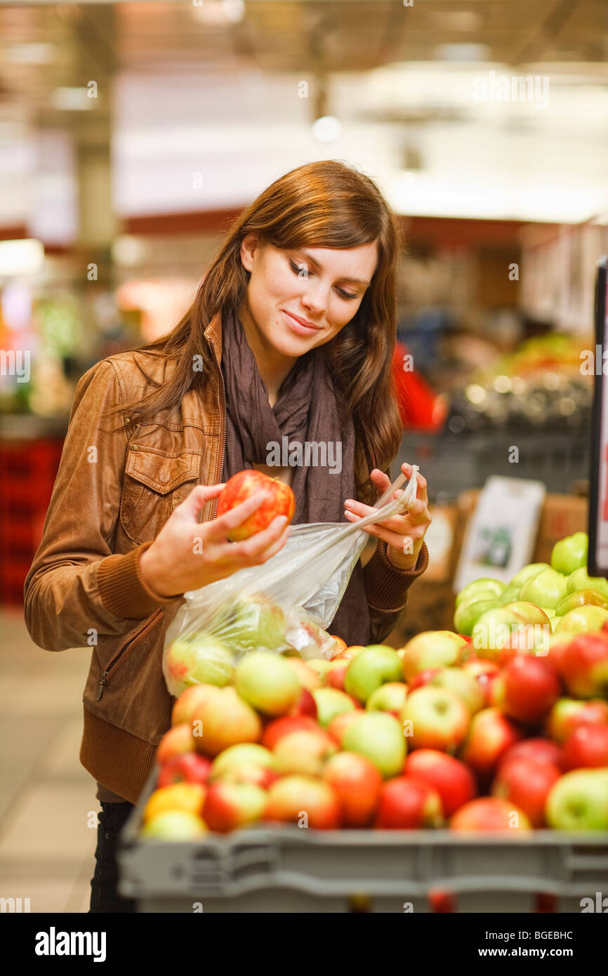 A woman in a grocery store is examining an apple before purchase. - Stock Image