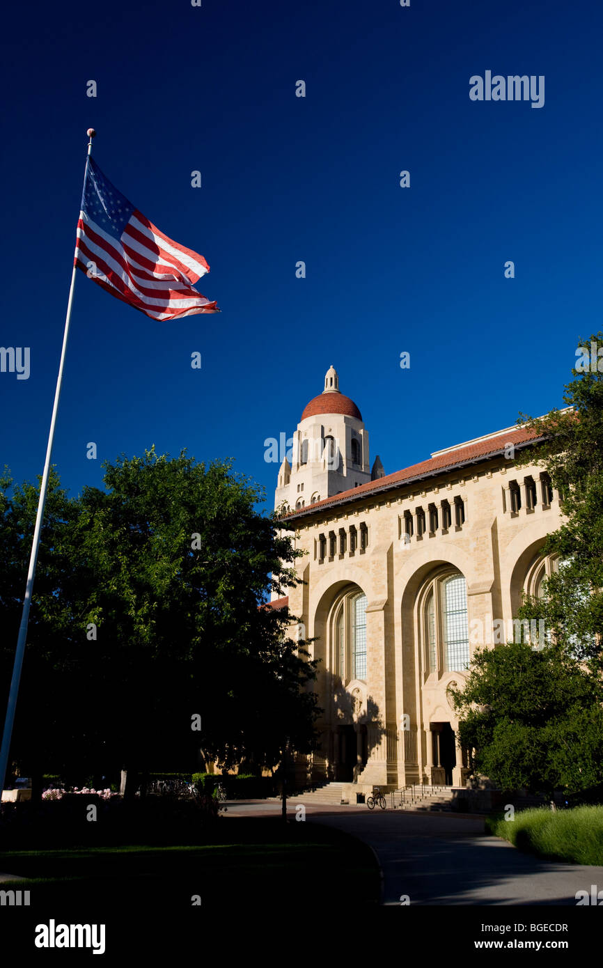 Hoover Tower stands behind an American flag at Stanford University on a clear day with blue skies, Stanford, California, Stock Photo