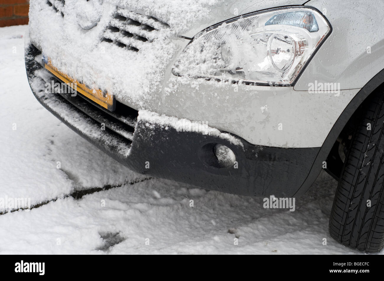 Detail of a snow covered car parked at the side of a road Stock Photo