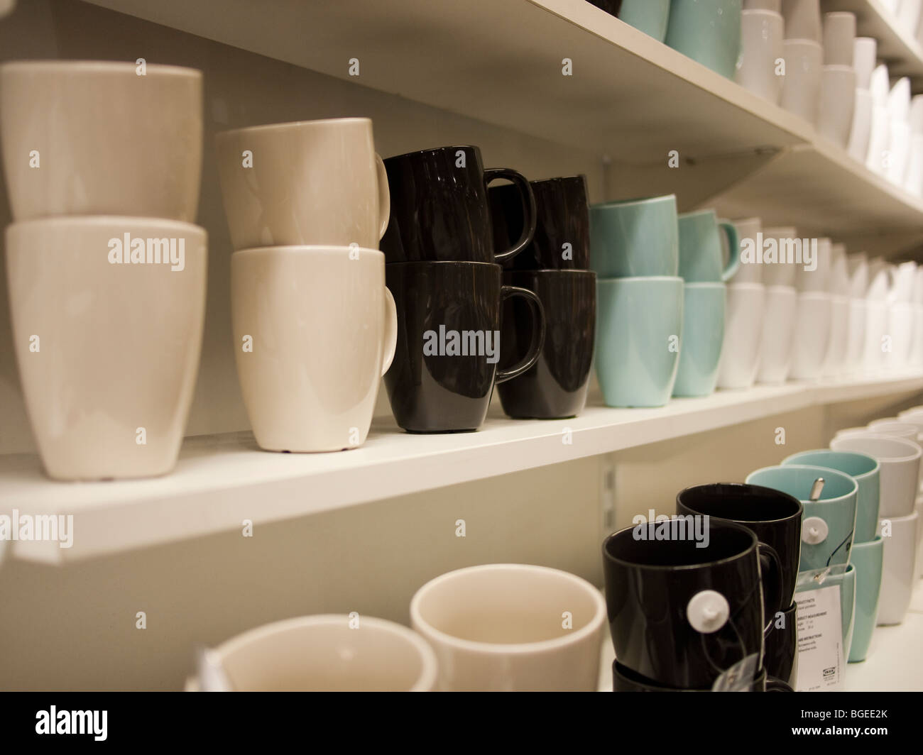 Rows of coloured cups on shelves - Stock Image