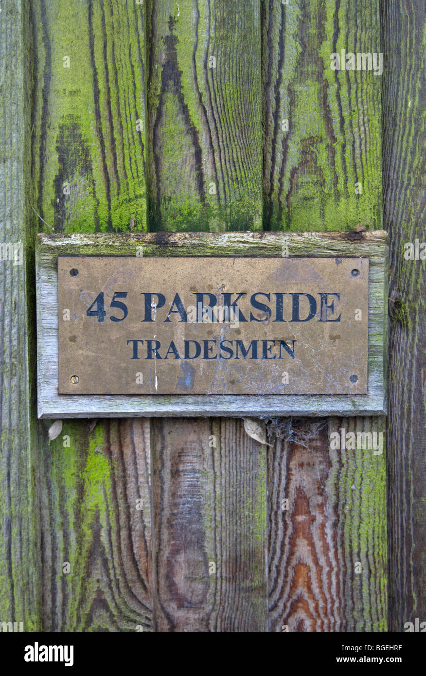 sign on wooden gate marking entrance for tradesmen at the back of a house in wimbledon, southwest london, england - Stock Image