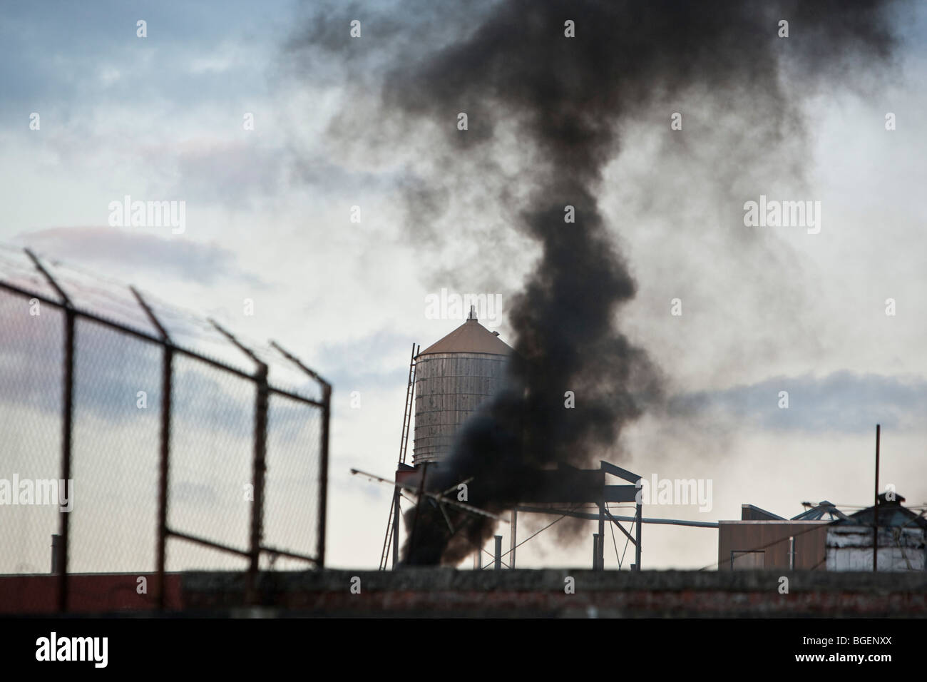Black smoke belches out into the sky from the roof top of a building on West 143rd street in New York, USA, 28 December Stock Photo
