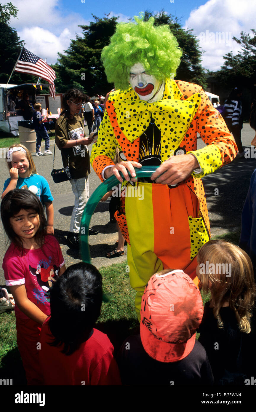 Colorful Clown entertaining young children at the Amador County Fair. - Stock Image
