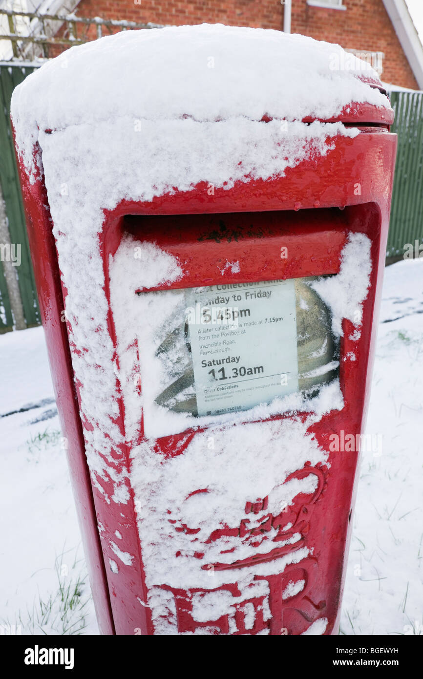 England, Britain, UK. Red postbox covered in snow in winter - Stock Image