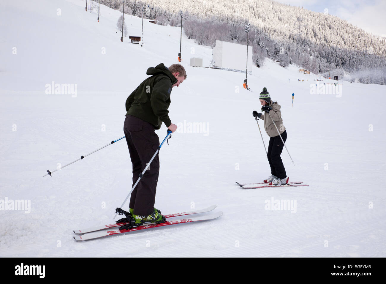 Novice skier learning to ski with personal instructor on snow covered nursery slopes in Austrian Alps. St Anton - Stock Image