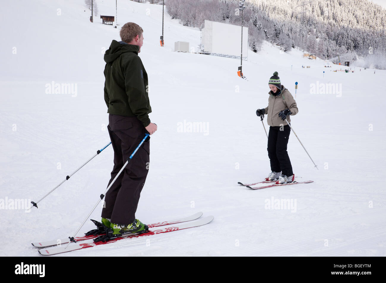 Novice skier learning to ski with personal instructor on snow covered nursery slopes in Austrian Alps. - Stock Image
