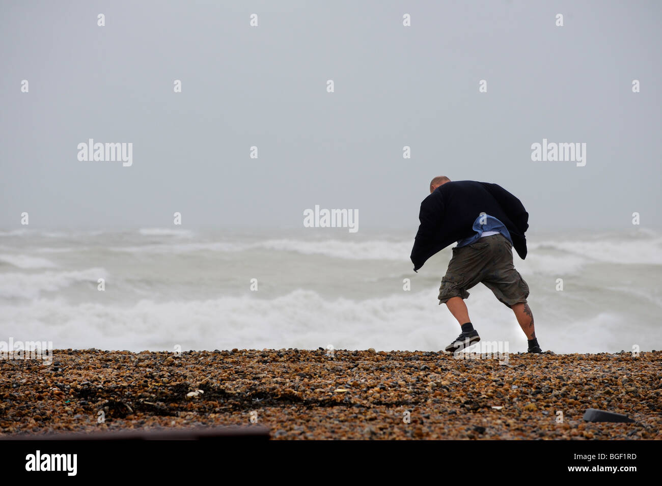 Stormy weather at Seaford in Sussex attracts people to the beach. This man is seen struggling to walk in the gale - Stock Image
