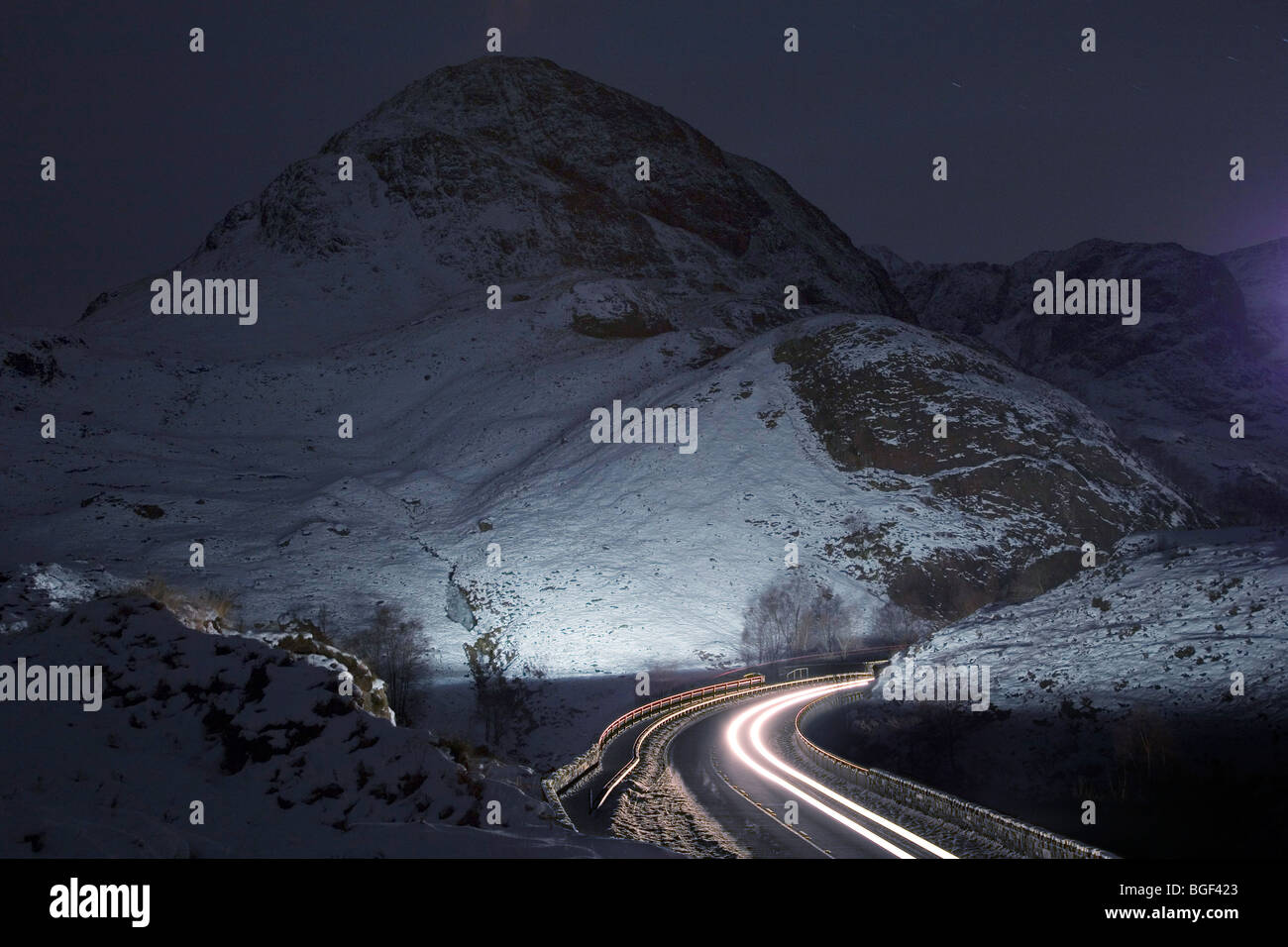 Traffic moves through the Pass of Glencoe, Scotland at night fall following the end of the Christmas holidays. - Stock Image