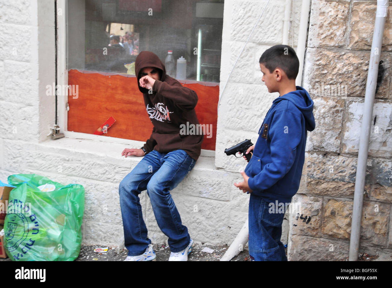 Young Arab Boy points a hand gun at the crowd - Stock Image
