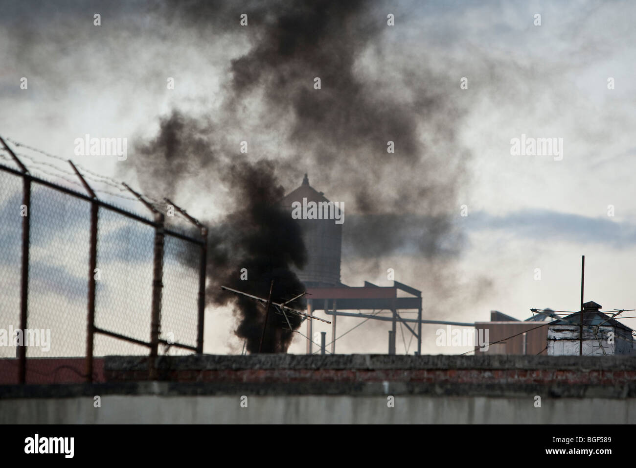 Black smoke belches out from the top of a building on West 143rd street in New York, USA, 28 December 2009. Stock Photo